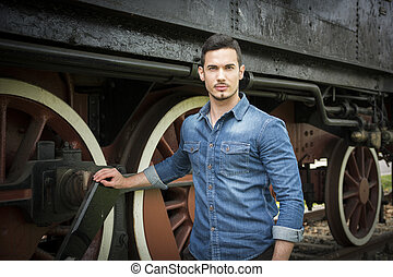 Handsome young man in denim shirt in front of old train,...