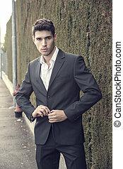 Handsome young man in elegant business suit standing outdoor