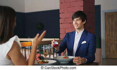 Handsome young man in fancy suit is making proposal to his...