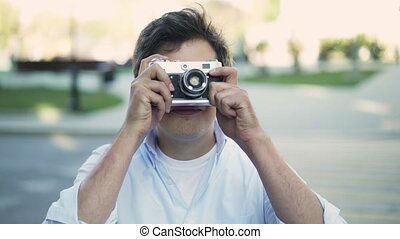 Handsome young man in glasses taking a shot with vintage camera and smiling