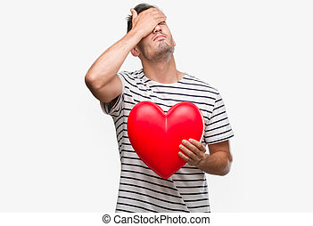 Handsome young man in love holding red heart stressed with hand on head, shocked with shame and surprise face, angry and frustrated. Fear and upset for mistake.