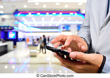Handsome young man in shopping mall using mobile Phone....