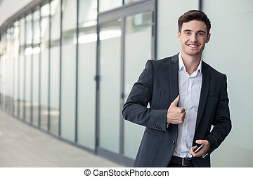 Handsome young man in suit is gesturing positively