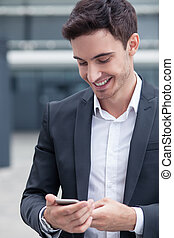 Handsome young man in suit is using telephone