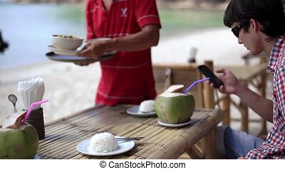 Handsome young man in sunglasses drink fresh coconut juice in a beach cafe and uses mobile phone while waiter brings tom yam soup with rice. 1920x1080