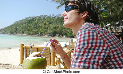 Handsome young man in sunglasses drink fresh coconut juice in a beach cafe with sea view