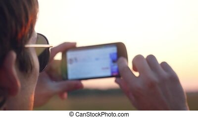 Handsome young man in sunglasses holds cell mobile phone take photo of wheat field on the sunset sky  in rural meadow