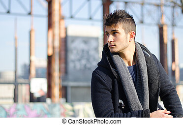 Handsome young man in urban or industrial setting, large copyspace
