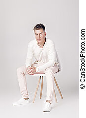 handsome young man in white sweater sits on a chair on