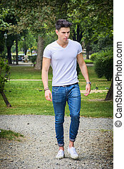 Handsome young man in white t-shirt outdoor in city park