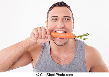 Handsome young man is eating healthy vegetable