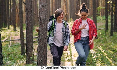 Handsome young man is hiking with his friend cheerful young...