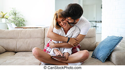 Handsome young man is hugging and kissing his beautiful wife