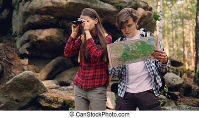 Handsome young man is looking at map while his friend is...