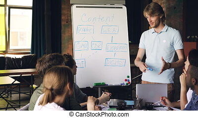 Handsome young man is making creative presentation for team using whiteboard, he is pointing at text with marker and talking. Business trainer and office concept.