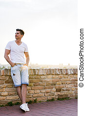 Handsome young man leaning against a brick wall