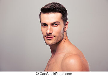 Handsome young man looking at camera over gray background