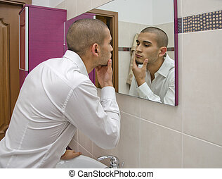Handsome young man looking at himself in bathroom mirror