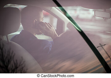Handsome young man looking at his cellphone while at the wheel of his car