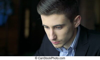 Handsome young man looking on and thinking in cafe