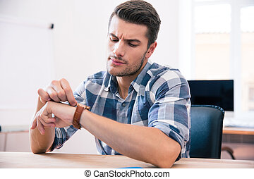 Handsome young man looking on wrist watch - Handsome young...