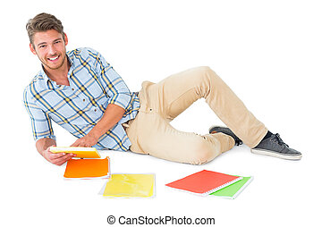 Handsome young man lying and studying