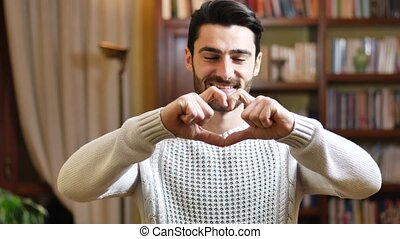 Handsome young man making heart sign with hands - Handsome...