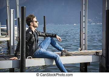 Handsome young man on lake in a sunny, peaceful