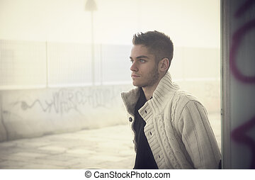Handsome young man outdoor in city setting, with winter clothes