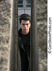 Handsome young man outdoor seen between two walls or stones
