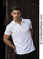 Handsome young man outside against wood door