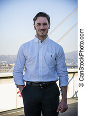 Handsome young man outside wearing white shirt