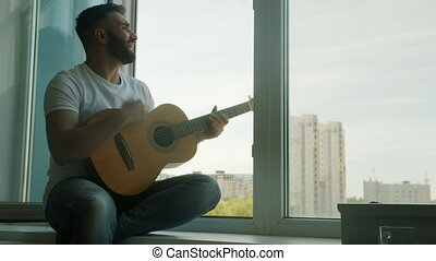 Handsome young man is playing acoustic guitar and singing having fun sitting on window sill at home alone. Entertainment and musical instruments concept.
