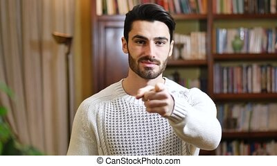 Handsome young man pointing finger at you, smiling