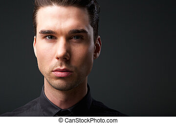 Handsome young man posing against gray background