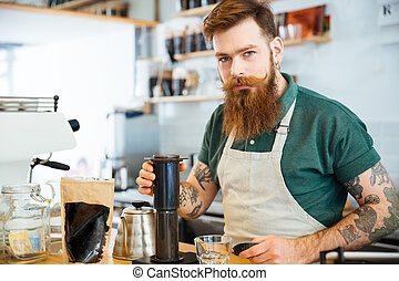 Handsome young man preparing coffee