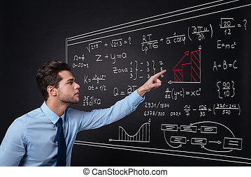 Handsome young man presenting equations.