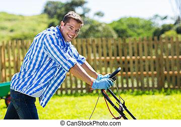 young man pushing lawnmower