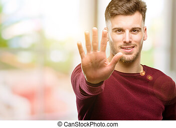 Handsome young man raising his finger, is the number five