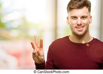 Handsome young man raising his finger, is the number three