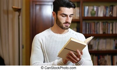 Handsome young man reading book at home in his living-room