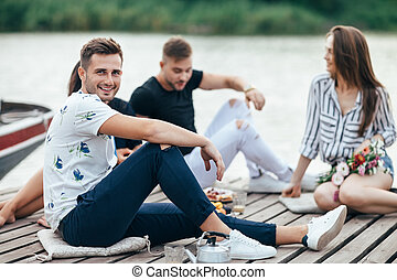 Handsome young man relaxing on wooden pier