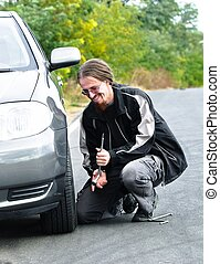 Handsome young man repairing car