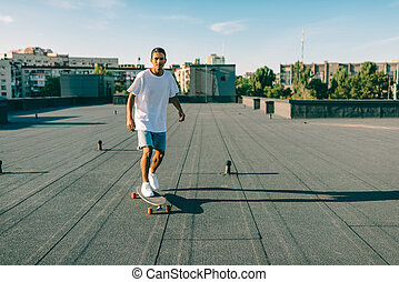 man riding skateboard on rooftop