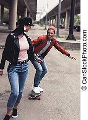 man riding to girlfriend on skateboard