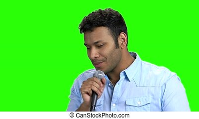 Handsome young man singing with microphone.