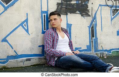 Handsome young man sitting against colorful graffiti