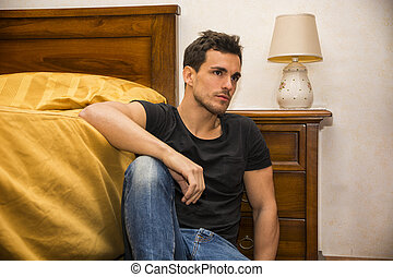 Handsome young man sitting by his bed