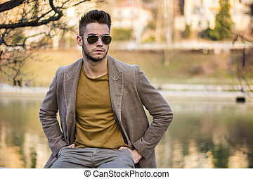 Handsome young man sitting by river in city