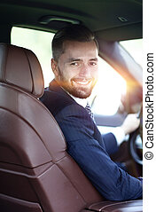 Handsome young man sitting in the front seat of a car looking at